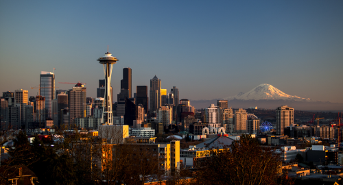 Seattle with a mountain in the background.                    The mountain has snow on it.                    A building, which might be a UFO, is in the foreground.                    Picture CC-BY tiffany98101.